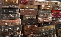Many vintage weathered leather suitcases on top of eachother