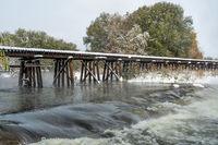 Wooden railroad trestle across a river