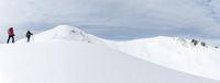 Senior couple is snowshoe hiking in alpine snow winter mountains panorama. Allgau, Bavaria, Germany.