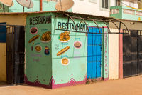 BIJILO, GAMBIA-January 06, 2020: Mural on a facade representing the dishes sold in a restaurant