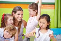 Lächelnde Erzieherin mit Kindern im Kindergarten