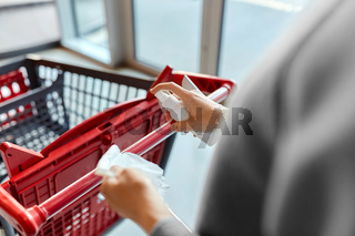 woman cleaning shopping cart handle with sanitizer