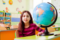 Schoolgirl sitting near globe on desk in classroom