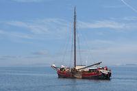 Traditional wooden sailing ship with passengers sailing at Dutch sea
