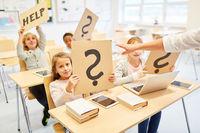 Kinder in Klasse von Grundschule halten Fragezeichen