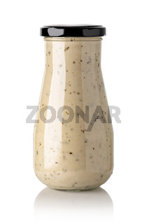Closed glass jar of white garlic and herb sauce