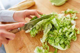 Hände beim Salat schneiden für Mittagessen in Küche