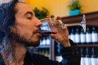 man enjoy the taste of glass of red wine