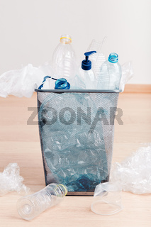 Heap of plastic bottles, cups, bags collected to recycling in a metal bin