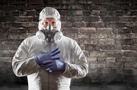 Man Wearing Hazmat Suit, Protective Gas Mask and Goggles Against Brick Wall