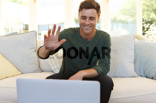 Caucasian man having video call waving and smiling to laptop in living room