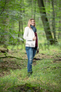 young woman standing in the green forest