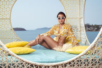 Fashion outdoor photo of beautiful girl posing on the wicker nest chair