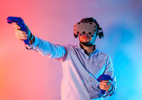 Young man using the virtual reality glasses and two gamepad