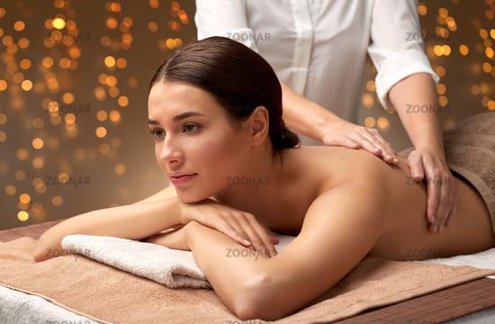 woman lying and having back massage at spa