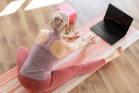 woman with laptop exercising at yoga studio