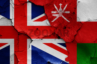 flags of UK and Oman painted on cracked wall