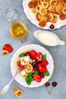 Porridge of tiny pancakes with berries, cream and honey.