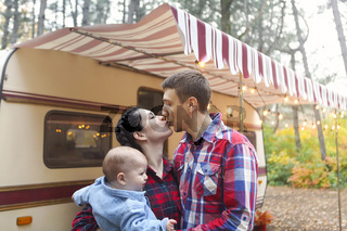 Portrait of a young smiling family while hugging near house on wheels