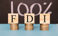 Finance Concept with Stack of Coins - 100 percent FDI or Foreign Direct Investment on wooden blocks.