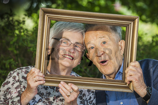 Retired couple posing behind a frame