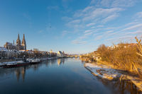 The famous skyline of the bavarian town Regensburg with the danube river on sunny winter morning with snow and ice