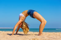 Young woman bend backwards on egyptian beach