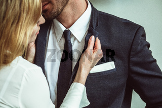 Young businesswoman holding jacket collar of businessman. Flirting couple of unrecognizable caucasian people. Passionate love affair in office workplace. Close up shot