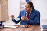 Hungry male employee eating buckwheat during break