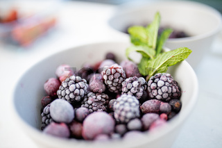 Bowl of dark berries and mint on a white table