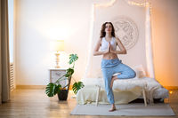 Smiling young brown haired woman in pajamas practicing yoga
