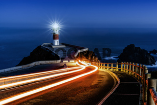 trailing car lights lead to Cabo Ortegal lighthouse at night