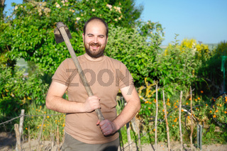 An adult male farmer with a hoe posing in the the farm.
