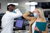 Businessman and businesswoman wearing face masks greeting each other by touch elbows at office