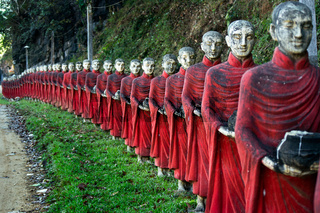 A long row of colourful buddhist monk statues at the entrance of the Kaw Ka Thaung cave temple.