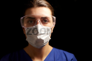 female doctor or nurse in goggles and face mask