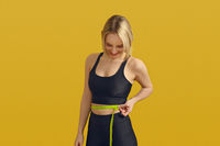 Slim sporty young woman measuring her waist