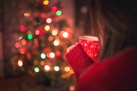 Young woman with cup of hot chocolate or tea or coffee in front of Christmas tree. Relaxing and christmas concept.