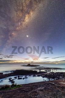Starry night sky just before sunrise of coastal landscape