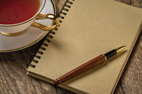 blank spiral notebook with pen and tea