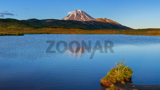 Panorama volcano landscape - reflection of mountains in alpine lake