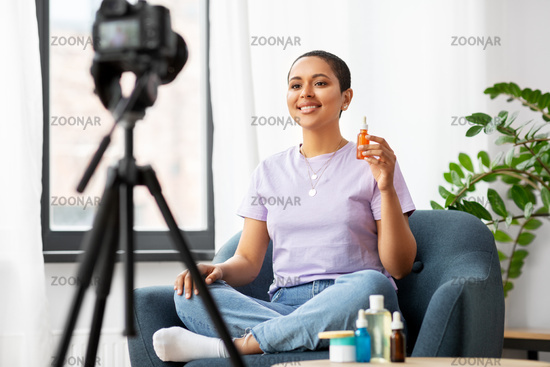 female beauty blogger with camera and cosmetics