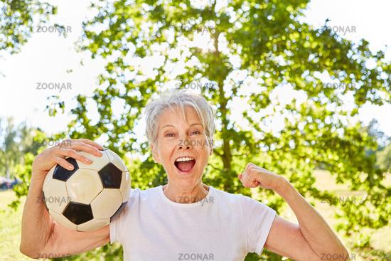 Vitale Seniorin mit Fußball jubelt nach einem Spiel