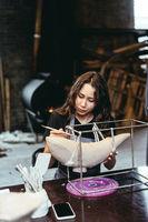 Portrait of young woman enjoying favorite job in workshop.
