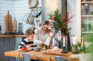 Mother with son in kitchen during Christmas holidays