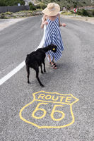 Young attractive woman wearing striped summer dress and straw hat standing on an endless straight empty road in the middle of nowhere on the Route 66 road and feeding black sheep.