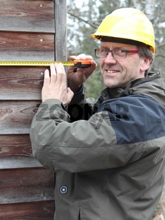 Ingenieur untersucht ein Holzhaus