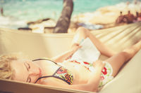 Lady napping on hammock at the beach.