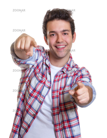 Laughing hispanic guy pointing with both hands at
