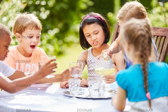 Kinder trinken Wasser bei Geburtstagsfeier